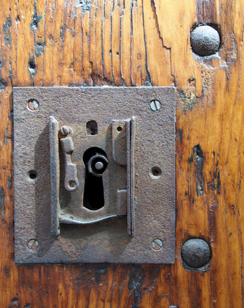 a large square rusty iron lock with keyhole in an old varnished wooden door with the end of the key visible and metal rivets