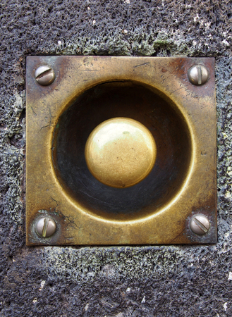 a close up of an old tarnished doorbell button with screws in a grey house wall