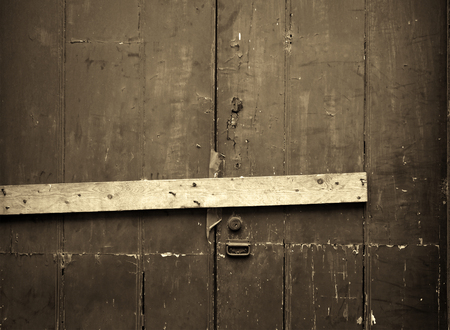 sepia close up of an old cracked peeling wooden plank door barred shut with a piece of timber and rusty nails with a lock and handle