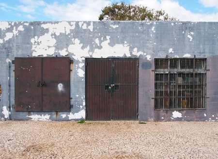 an old low run down grey painted storage building with rusty metal bars and closed metal security shutters padlocks on the door