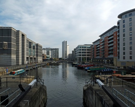a view of leeds dock from the lock gates showing waterside developments offices and apartment buildings with houseboats moored in the water