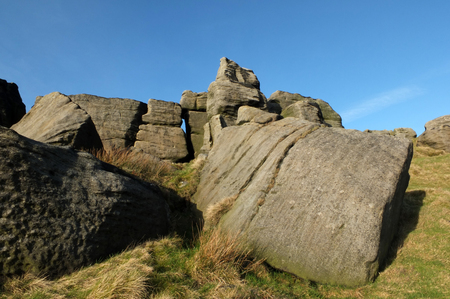 large rugged gritstone outcrop at the bridestones a large rock formation in west yorkshire near todmordenwith blue sky and surrounding countryside