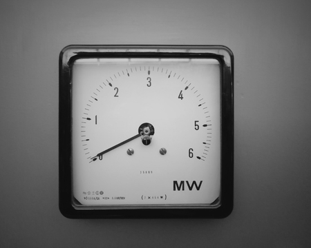 an old square industrial wattmeter with the scale measured in milliwatts with an analogue dial and scale on a grey background
