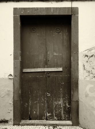 a sepia monochrome image of an old weathered wooden door nailed shut with a wooden bar and flaking paint on an outside wall