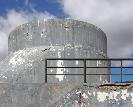 an old crumbling concrete military bunker type structure with rounded windowless surfaces and a green railing against a blue cloudy sky 写真素材