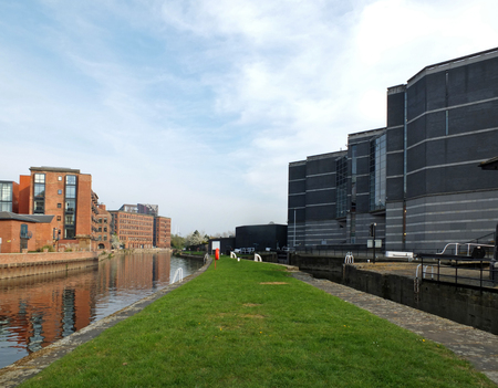the leeds lock entrance to clarence dock with footbridge over the river aire and historic gates and mooring area surrounded by modern apartment developments