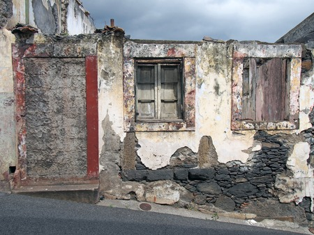 an old ruined house partly collapsed on a sloping street with a blocked up door crumbling walls and fading red painted windows with closed shutters