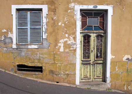 the front of an old abandoned yellow house with blue shuttered windows and locked green wooden door with flaking peeling paint on a sloping street Stock Photo