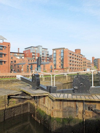 old wooden lock gates on the canal in leeds city center surrounded by waterside apartment buildings