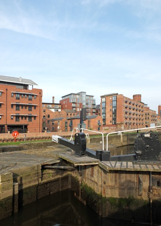 old wooden lock gates on the canal in leeds city center surrounded by waterside apartment buildings Stock Photo