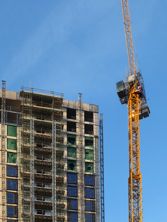 a tall yellow construction crane working on a large hight rise concrete building with scaffolding against a blue sky