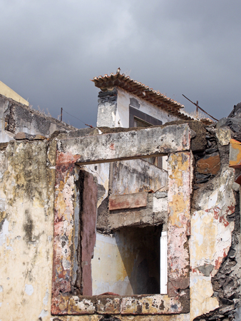 close up a window of a collapsing abandoned roofless house with broken walls and grey sky