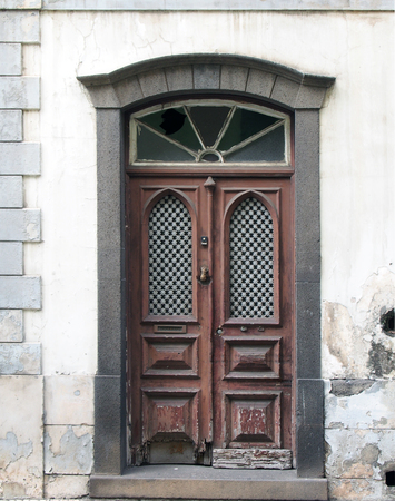 an old ornate brown double house door with broken repaired panels and hand shaped knocker with stone frame and doorstep