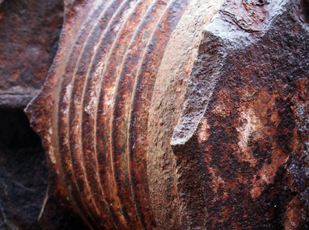 A close up of rusting brown steel machinery with rough texture and grooves