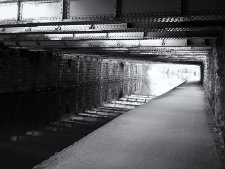 Monochrome view under an old low steel girder bridge crossing the leeds to liverpool canal near armley with stone wall and a narrow footpath alongside the water 스톡 콘텐츠