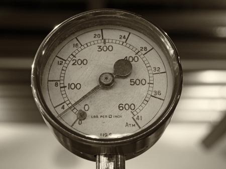 Image monochrome sépia d'un vieux manomètre rond en laiton brillant avec un cadran rond marqué en chiffres