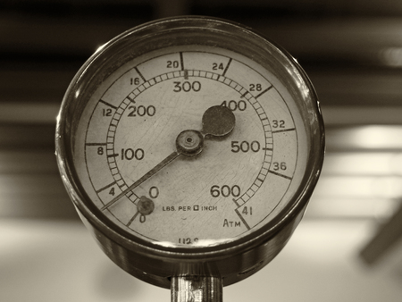 Sepia monochrome image of an old shiny brass round pressure gauge with a round dial marked in numbers