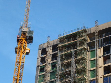 Yellow construction crane next to a large concrete building under construction with scaffolding and hoist towers Imagens