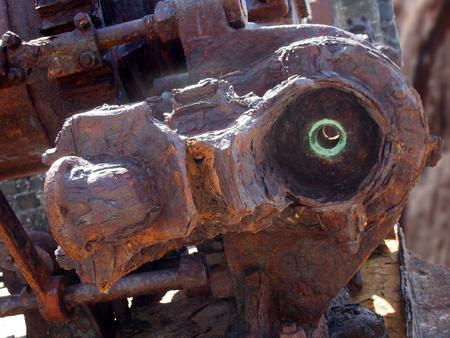 Gros plan d'un grand moteur industriel cassé rouillé avec des boulons et des engrenages à l'extérieur