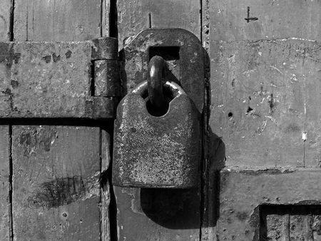 A monochrome close up of an old rusty closed padlock and hasp on a distressed wooden plank door