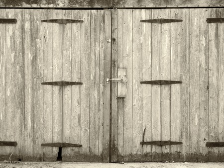 Monochrome old rural grey plank wooden plank doors with a bolt fastening and rusty iron hinges Stock fotó