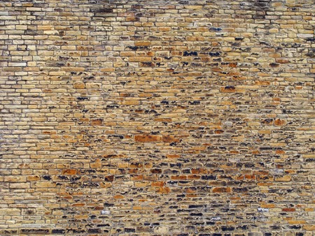 brown and yellow outdoor stone wall with many uneven rough bricks and textured surface