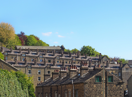 streets of terraced stone houses on a hillside surrounded by trees with a blue summer sky in hebden bridge west yorkshire Stock Photo - 124727139