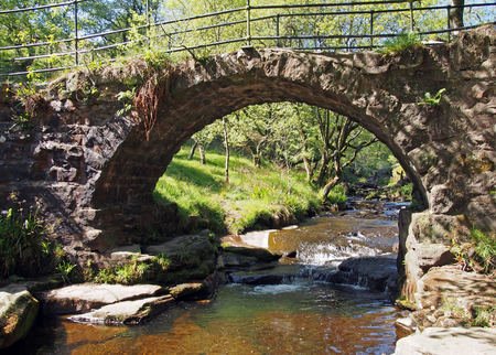 the old packhorse bridge at lumb hole falls a waterfall in woodland at crimsworth dean near pecket well in calderdale west yorkshire