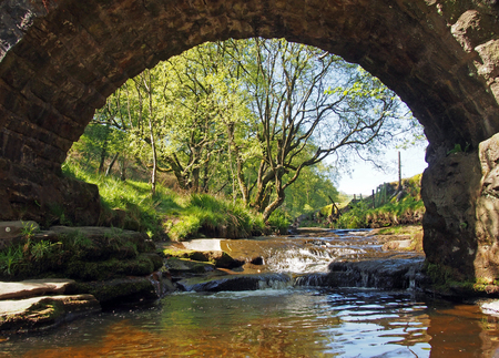 ta view under the old packhorse bridge at lumb hole falls in woodland at crimsworth dean near pecket well in calderdale west yorkshire 写真素材