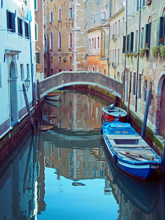 a quiet narrow canal crossed by a bridge with moored boats and old buildings reflected in the water in Venice 写真素材