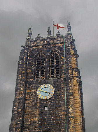 the tower and clock on halifax minster in west yorkshire against a grey cloudy sky with an english flag