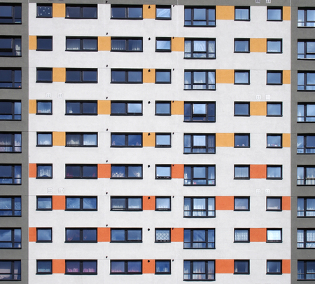 a full frame image of windows in a large high rise apartment building with repeating rows of windows with white walls with orange and grey details Reklamní fotografie