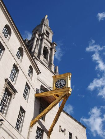 a close up of the tower and ornate gold clock on leeds civic hall in west yorkshire against a sunlit cloudy sky