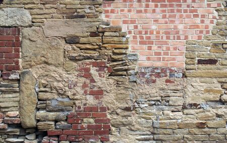 a large old wall made of mixed bricks and stone with many jumbled patched and uneven repairs