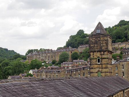 a view of the steep hillside streets in hebden bridge between summer trees with the tower of the historic nutclough mill building at the front 版權商用圖片