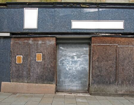 a street view of the front of an old abandoned shop with decaying boarded up windows covering the storefront and a closed steel shutter