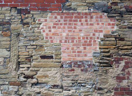 un grand vieux mur fait de briques et de pierre mélangées avec de nombreuses réparations patchées et inégales