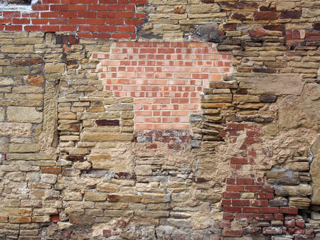 an old much repaired and patched wall mad of mixed types of bricks and stones
