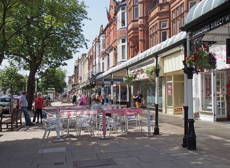 southport, merseyside, united kingdom - 28 june 2019: people sitting at outdoor cafes and walking past shops in the historic lord street shopping area in southport merseyside