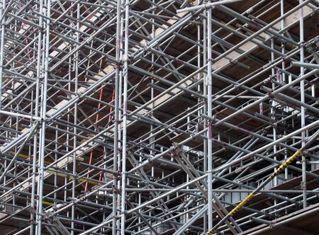 a dense network of metal scaffolding poles supporting work platforms on a construction site