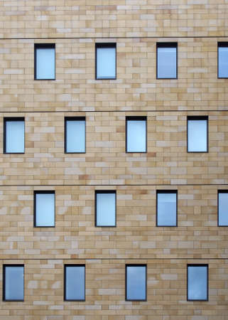 the facade of a modern stone building with geometric repeating pattern of small windows