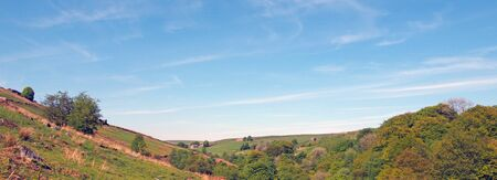 a long panoramic view of west yorkshire countryside with fields and moors above the woodland in hardcastle crags with a blue sunlit cloud sky 版權商用圖片