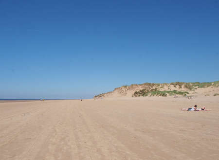 formby, merseyside, united kingdom - 28 june 2019: a view of the long sandy beach in formby merseyside on a bright summer day with blue sky with people sunbathing and grass covered dunes Stock Photo