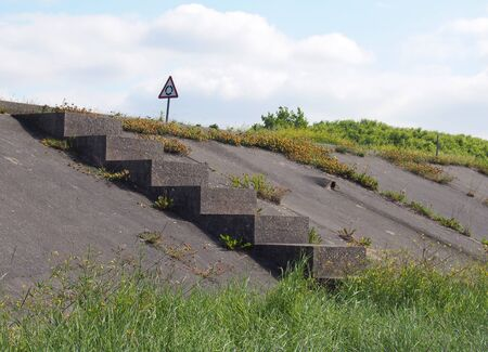 a concrete staircase surrounded by grass leading to a coastal road along the ribble estuary near southport merseyside with a roundabout traffic sign 版權商用圖片