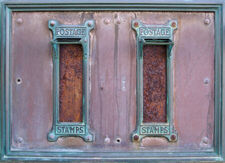 old british postal mail boxes with rusted letter slots and ornate green copper frames with the words postage stamps surrounded by an old stained metal frame