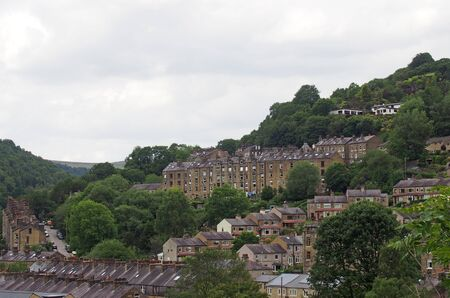 a view of the streets and houses of hebden bridge between trees and calder valley landscape in west yorkshire