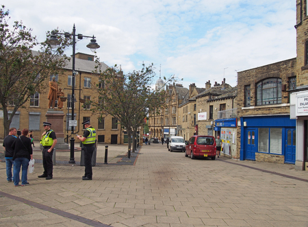 bradford, west yorkshire, united kingdom - 19 june 2019: police community support officers talk to people outside old buildings and shops in oastler square in bradford west yorkshire