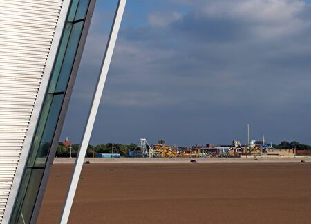 an architectural detail of southport pier with the beach at low tide and the historic amusement park in the distance against a blue summer sky