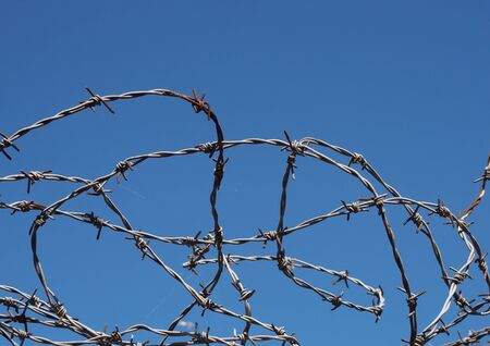 coiled twisted sharp barbed wire against a bight blue sky