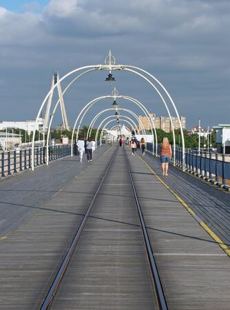 southport, merseyside, united kingdom - 28 july 2019: the historic pier in southport merseyside with people walking towards the town and the suspension bridge and buildings visible behind trees 写真素材